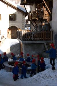 Kinder in blauen Hemden und mit roten Gipfelkappen umrunden mit ihren Schellen einen Brunnen im Dorf. Foto © Barbara Hutzl-Ronge