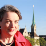 Im Vordergrund ist die Autorin Barbara Hutzl-Ronge zu sehen, im Hintergrund die Kirche Fraumünster und das Stadthaus in Zürich.