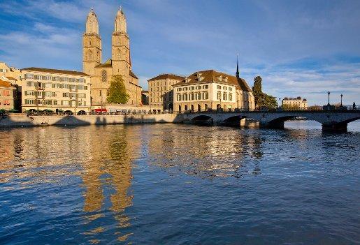 Magisches Zürich von seiner schönsten Seite! Die Türme vom Grossmünster spiegeln sich in der Abendsonne in der Limmat. am Brückenkopf das Helmhaus und die Wasserkirche mit dem Dachreiter. Zürich, Foto © Jan Geerk