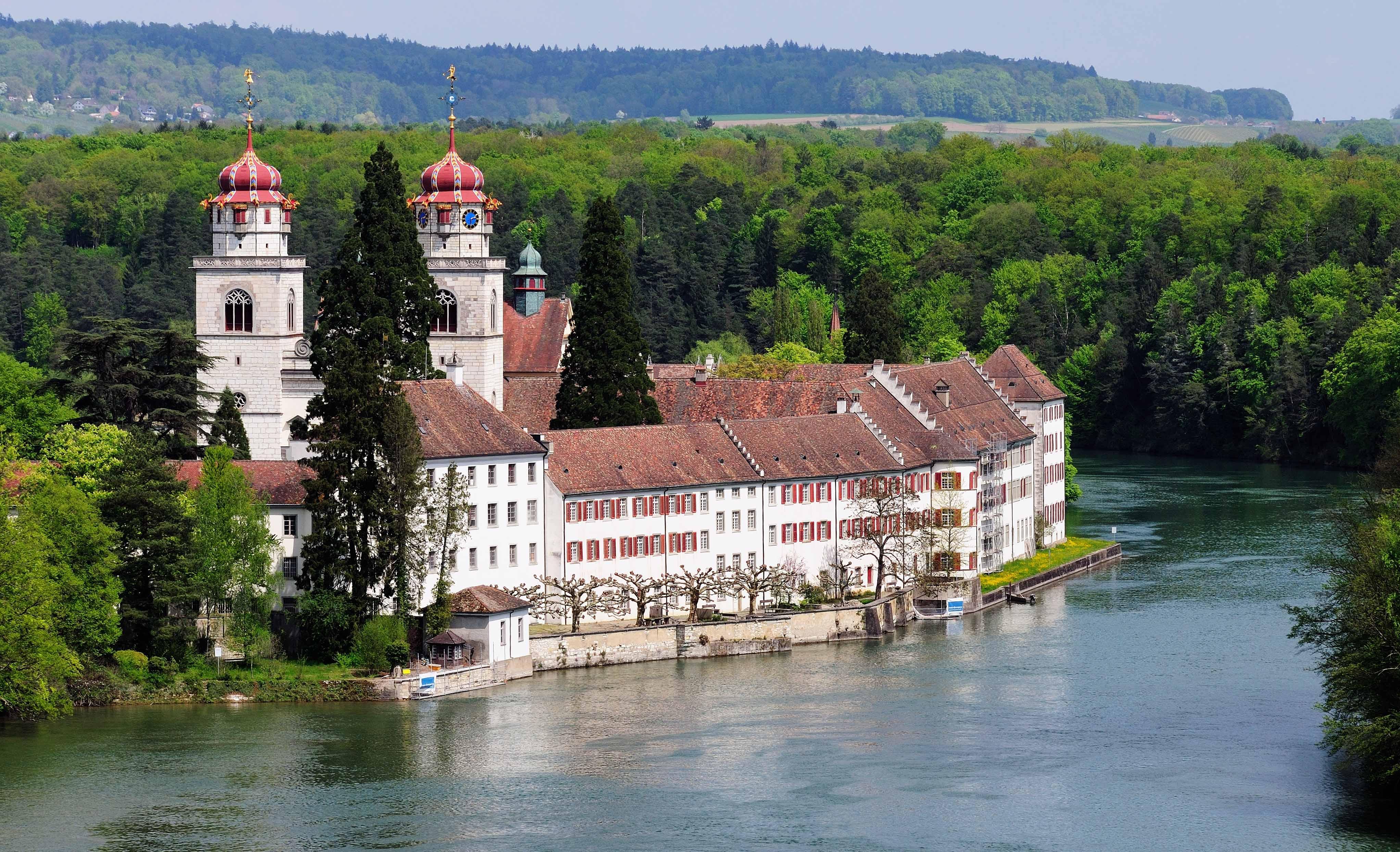 Die Klosterkirche mit den zwei roten Zwiebeltürmen und den Klostergebäuden auf der Insel im Rhein bei Rheinau