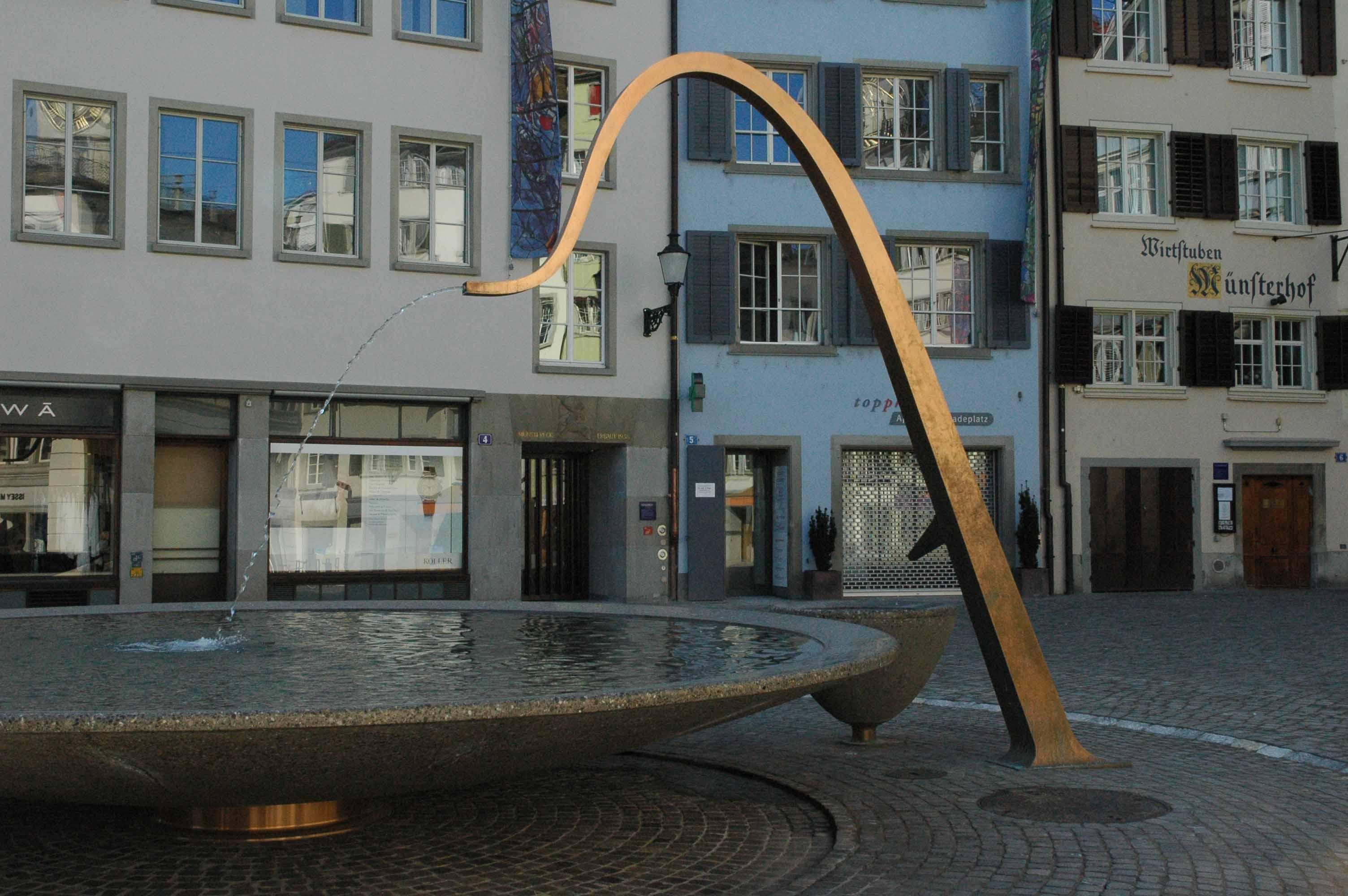 Durch ein markant geschwungenes kupfernes Brunnenrohr fliesst Wasser in ein grosses kreisrundes Becken auf dem Münsterhof in Zürich. Foto © Barbara Hutzl-Ronge