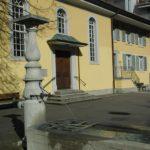 Brunnen aus Kalkstein vor der gelb gestrichenen Fassade mit drei hohen Kirchenfenstern des Bethüsli