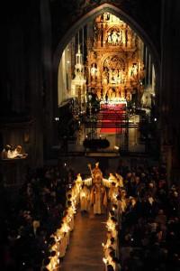 Blick von der Empore des Münsters in die nur von Kerzen erleuchtete Kirche, in der die Gläubigen das Nikolausfest feiern, © Foto Lauterwasser
