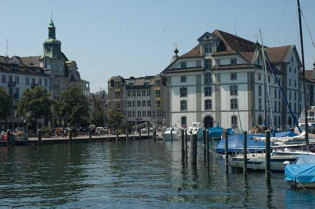 Hafeneinfahrt Rorschach: im Wasser vertäute Boote, das Kornhaus und die Promenade.