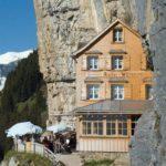 Das schmucke Gasthaus Äscher, wie ein Adlerhorst in den Fels gebaut, daneben Sonnenschirme auf der Terrasse