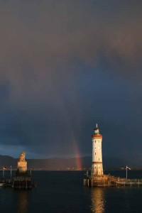 Dunkle Gewitterstimmung in Lindau, doch der Leuchtturm und der Löwe an der Hafeneinfahrt leuchten in der Sonne, dazwischen steigt ein Regenbogen in di die Wolken, Foto © B. Brechtel