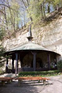Steilwand aus Sandstein, unten ein Rondell mit Dach und Dachreiter, die Kapelle Maria im Stein