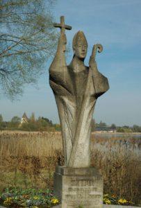 Statue des Hl. Pirmin auf der Insel Reichenau Reichenau. Im Hintergrund der Turm der Kirche St. Georg von Oberzell