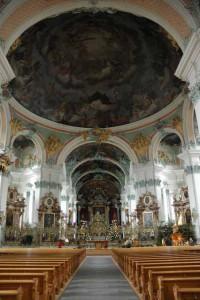 Innenraum der Kathedrale St. Gallen: Vom Mittelgang des Kirchenschiffs betrachtet sind ganz vorne der Hochaltar und vieri Seitenaltäre zu sehen, davor wölbt sich über die Besucher die Kuppel mit dem dunklen Himmelsbild samt aller St. Galler Heiligen