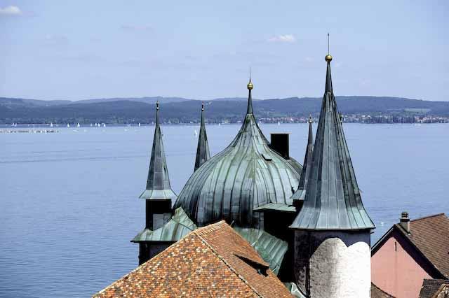 Dächerlandschaft in Steckborn: das dicke Zwiebeldach und vier spitze Turmdächer des Turmhofs, im Hintergrund der Untersee und das gegenüberliegende Ufer Steckborn