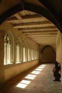 Durch Spitzbogenfenster fällt Sonne aus dem Garten auf den Boden des Kreuzgangs. Kloster St. Georgen, Stein am Rhein