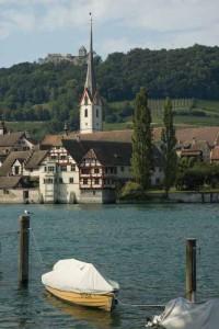 Ein Ruderboot, vertäut am Rheinufer, am gegenüber liegenden Ufer Kloster St. Georgen, Stadtkirche und Burg Hohenklingen, Stein am Rhein.