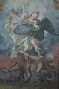 Der Erzengel Michael kämpft mit flammendem Schwert gegen Luzifer, der sich unter ihm windet.