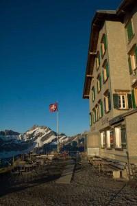 Berggasthaus Schäfler im Morgenlicht. Die Fensterläden leuchten grün, der Himmel ist tiefblau und die rote Fahne mit weissem Kreuz steht stramm im Wind