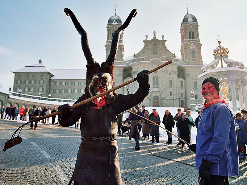 Unbändige Teufel tanzen am Güdelmontag beim Sühudiumzug auf dem Klosterplatz in Einsiedeln