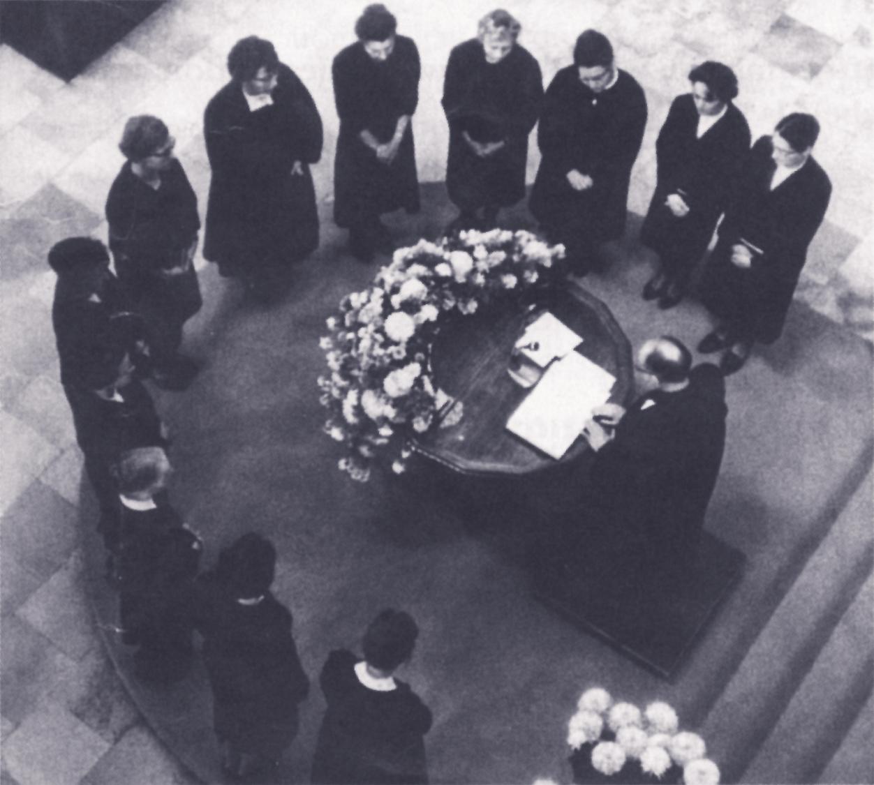 Zwölf Theologinnen, manche von ihnen seit Jahrzehnten im kirchlichen Dienst, stehen um den Taufstein im Grossmünster und werden von Kirchenratspräsidenten Robert Kurtz 1963 ordiniert. Foto: Zürcher Kirchenbote
