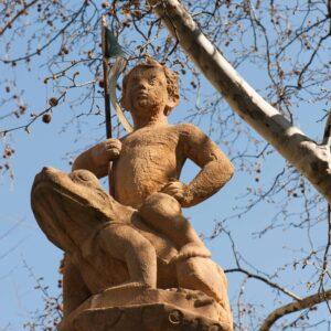 Brunnenfigur: auf einem Frosch sitzt ein Knabe und hält triumphierend ein Fähnlein
