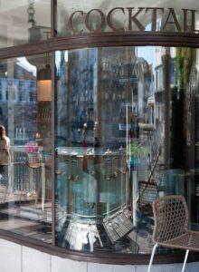 Im Fenster der Barchetta Bar vom Hotel Storchen in Zürich, spiegeln sich die Limmat und die Zunfthäuser an ihrem Ufer