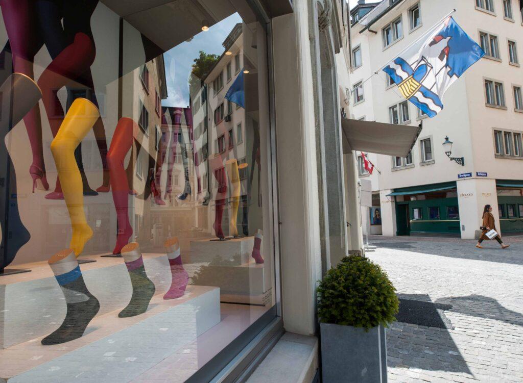 Im Schaufenster eines Strumpfgeschäfts in Zürich, spiegelt sich der Rennweg, wo die hugenottischen Strumpfweber wohnten.