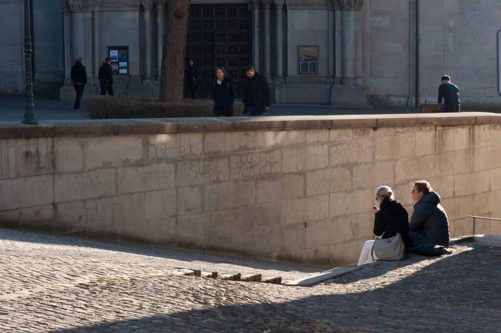 Gemütlich sitzen zwei Passanten auf der Treppe. Ein sanfter Rosaton liegt auf den Pflastersteinen der Gasse im Sonnenlicht. Dahinter im Schatten steht das Grossmünster im Schatten und eine zauberhafte Ruhe liegt über den Zwingliplatz