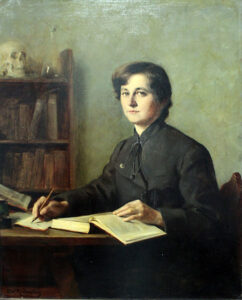 Mit einer Hand blättert sie im Buch, mit der anderen Hand macht sie sich Notizen. Selbstbewusst blickt die Doktorandin Elisabeth Winterhalter zu Ottilie Roederstein, die sie porträtiert